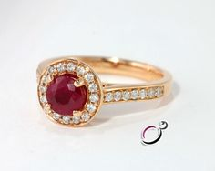Divine 0.80ct ruby surrounded beautifully by a halo of round cut diamonds,set on an 18k yellow gold band accented on either shoulder by additional diamonds bringing the total carat weight to 1.15.