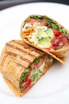 Veggie wrap with hummus, roasted red bell peppers, spinach, chopped tomatoes, avocado, and shredded mozzarella wrapped up in a sundries tomato tortilla and lightly grilled in a panini press.