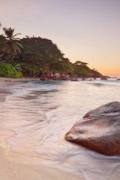 Ando en la playa junto a una roca viendo el mar