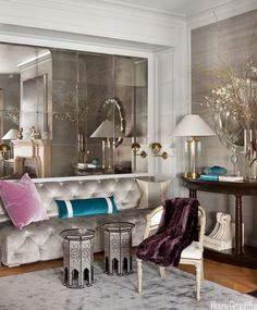 """Designer Benjamin Dhong transformed the living room of a San Francisco row house by replacing cabinets with """"the relaxed elegance"""" of a custom banquette in velvet and antiqued mirrors. The space becomes intimate for entertaining — """"I think it's geared to Champagne and cocktails, flirting and seduction,"""" he says. """"You're enveloped, floating inside the cloud with the silver lining.""""   - HouseBeautiful.com"""