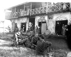 WWII soldiers taking a break from march through Burmese jungle in front of tea house. Photographer Unknown