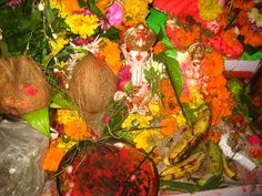 Ganesh amid colorful flowers and offerings.