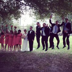 Bridal party photo with coral bridesmaid dresses and groomsmen jumping