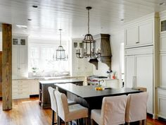 It's the mix of woods, including heart-pine flooring and recycled-timber beams, that distinguish this country kitchen by Studio Entourage and architect Linda MacArthur. The barstools are slipcovered in muslin for a casual look and easy care.