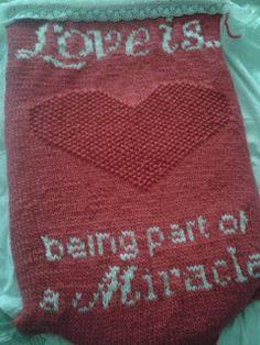 Knitting baby blanket. Een gebreide baby deken met tekst.