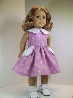 1950's Dress for American Girl Dolls from agseamstress. This sleeveless cotton dress in a lovely lilac dainty print features a large white collar edged in white crochet lace. The same white fabric and trim cuffs the two deep skirt pockets. A little self belt with a plastic buckles circles the waist.