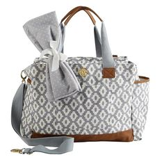 Stow your newborn's diapers, toiletries, and more in this stylish canvas bag, showcasing a matching changing pad and cross body strap.