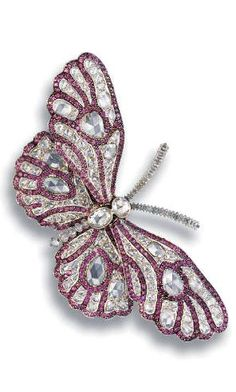 A DIAMOND AND RHODOLITE GARNET BUTTERFLY CLIP BROOCH, BY CARNET  Designed as articulated wings bezel-set with vari-shaped rose-cut diamonds to the pavé-set rhodolite garnet veins, with a bezel-set oval-shaped rose-cut diamond and diamond rondelle body, extending with diamond rondelle antennae, mounted in platinum, 9.5 cm long, in a Carnet purple leather case