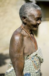 Elaborate palm frond tattoos adorn the arms of this elderly Makonde woman.