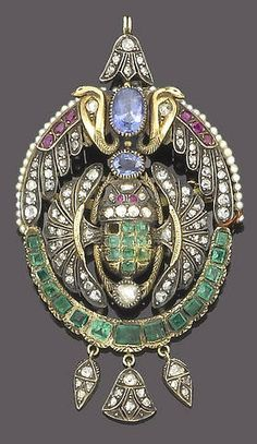 A gem-set and seed pearl brooch pendant, circa 1900  The elaborate openwork plaque decorated with variously cut diamonds, emeralds, rubies and seed pearls, centrally set with two oval mixed-cut sapphires between opposing cobras rising above a scarab with splayed wings set with square-cut emeralds, rose-cut diamonds and circular-cut ruby eyes, terminating in three articulated drops set with rose-cut diamonds.