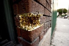 """This street Art project is called """"Urban Geode"""" and is done by 'A common Name' that started in Los Angeles. They created this """"Urban Geode"""" from paper or resin in 3-Dimensional sculpture forms. The finished shapes looks like geodes, crystal, quartz, or any mineral formation. They fit in every little hole of buildings or pipes of urban infrastructures. Behind """"A common Name"""" and """"Urban Geode"""" project, there is Paige Smith, a freelance artist and graphic designer from Los Angeles."""