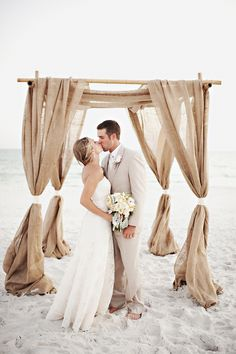 Fantastic use of burlap for a beach wedding! 4 pole ceremony structure tied with white bands.