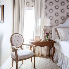Elegant bedroom features a wallpapered accent wall lined with a white curved headboard on bed dressed in a white linen duvet, monogrammed shams and a white linen bedskirt next to a French nightstand with cabriole legs placed before windows dressed in white and grays tripe drapes alongside a lilac velvet tufted round back chair atop a gray trellis rug.