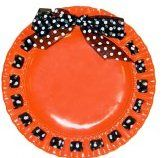 Decorate a paper plate with ribbon to display Halloween treats on