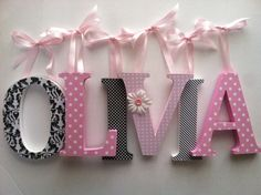 *PRICE IN LISTING IS PER 6 INCH LETTER Spell out your childs name with these adorable pink and black letters! These letters will look great sitting on a shelf or a bookcase or hanging on a wall in your little ones nursery. The letters in this listing are 6 inches tall and are $14.00 per letter. These letters are hand painted using non-toxic acrylic paints. The letters are covered with quality scrapbook paper and then each letter is sanded by hand. They can be embellished with ribbons…