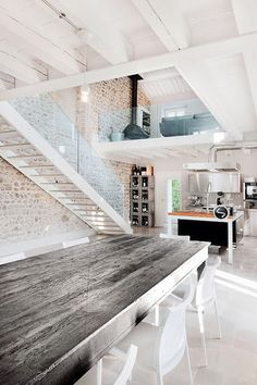 open loft home, with brick walls, a big wooden table, a cast iron stove