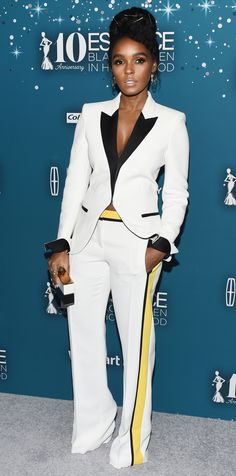 Janelle Monae is a pro when it comes to fun fashion. Exhibit A: her contrasting power suit with sharp lapels, inverted sleeve detailing, and bright yellow trim. The actress/musician topped off the look with a black and white hard case clutch and gold jewelry. Look closer and spot the paperclip earrings!