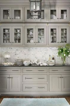 Light gray butler pantry features glass front cabinets with black hardware over . Light gray butler pantry features glass front cabinets with black hardware over Carrera marble mini brick tiles creating a stunning backsplash. Kitchen Remodel Small, Country Kitchen, Backsplash For White Cabinets, Kitchen Tiles Backsplash, Kitchen Renovation, Country Kitchen Lighting, Black Countertops, Kitchen Design, French Country Kitchens