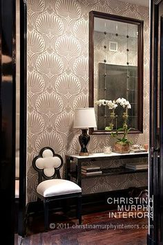 Gorgeous foyer with taupe and ivory Art Deco style wallpaper and hardwood floors. The foyer features a black lacquered console table with white top. The console is topped with stacked books, a white orchid and a glossy black table lamp. A large traditional style mirror hangs over the console table. A Suzanne Kasler Alexandra Side Chair flanks the console table