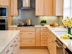 THE COMPROMISE Mable cabinets with Different Color Back Splash, and White Island and modern Pulls