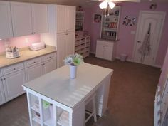 Craft room with white cabinets, work island and pink walls.