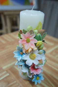 Vela decorada com flores do campo em biscuit.