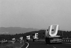 """Trucks carrying the large, precast concrete letters of Mansilla+Tuñón's Fine Arts museum of Castellón in order of their display in 1999.     """"As they moved through the landscape and the towns, the five letters formed a word.The emergence of a word, an intruder, implies a culturization of landscape through thought. A culturization in motion that leaves no lasting mark. An ephemeral action, limited to four hundred and forty kilometres and ten hours of travel."""""""