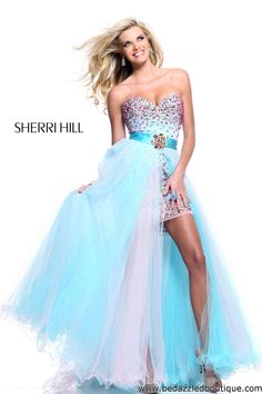 This high low gown has a bedazzled short dress underneath the flowing tulle skirting.