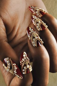 The Nail Art: Gold Chains and Rhinestones: A dark red polish base complements the sexy gold and rhinestone accents. Carter's influence was the subtle draping of the feminine Indian-inspired head chain Alicia Keys is known for wearing.