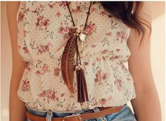 Floral top. Feather necklace.