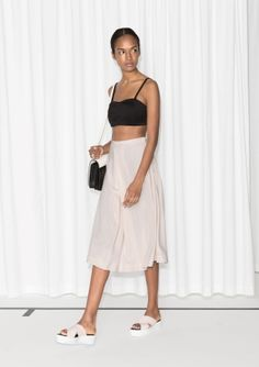 This wear-with-everything skirt has overlapping pleats at front and a flattering a-line silhouette that hits below the knee.