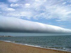 """""""Nuvem rolo"""" sobre o Uruguai    Esta é uma nuvem rolo. Ela forma-se em uma altura de 100m a 300m no solo e portanto é uma nuvem considerada baixa. Ainda não há um consenso sobre sua formação e a teoria mais aceita atualmente é de que o fenômeno acontece quando há o encontro de massas de ar vindas de direções contrárias, com temperaturas e umidades bem contrastantes."""
