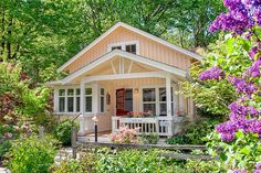 This is a gorgeous Kvale Hytte Cottage in the middle of a luxurious garden. Outside, you'll notice a rustic split-rail fence portioning off a lush garden. The creamy yellow board and batten e…