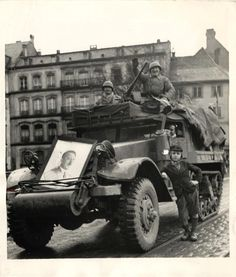 1944- Native boy poses beside Halftrac manned by French soldiers in Strasbourg. Note portrait of Hitler mounted on front.