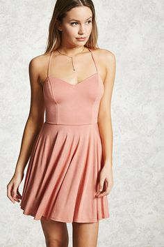 Style Deals - A knit cami dress featuring adjustable straps that cross in back, a V-neckline, and a fit & flare silhouette.