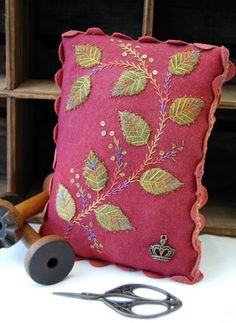 An easy beginners wool applique pincushion stitched in Cottage Garden 8# perle thread and enhanced with beads and sequins. The background and leaves are hand dyed felted wool fabric. The ric rac is hand dyed and embroidered. 22cm. x 16cm.