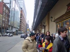 Cheap Theater Series will give you creative ideas on how to see theater, and other live performances at a low or even no cost.  Here are some people standing in for lottery tickets for Rent at the Cannon Theatre (now Ed Mirvish Theatre) in Toronto, Ontario.