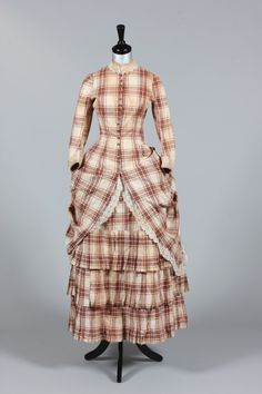 1875 Summer Dress Medium: cotton, mother of pearl A tartan cotton summer gown in princess-line with mother of pearl buttons, integral pleated skirt, the over skirt caught in a polonaised bustle. 1870s Fashion, Victorian Fashion, Vintage Fashion, Old Dresses, Cotton Dresses, Girls Dresses, Pioneer Dress, Edwardian Gowns, Summer Gowns