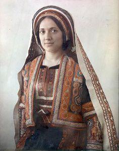 1929年から1946年頃、パレスチナ、ラマラの女性のカラー写真。パレスチナ周辺の民族衣装は刺繍に特徴があり、所属する集団ごとに図案やステッチが異なる。そのドレスは生涯を通じて着用されるため堅牢に作られていた。