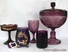 Amethyst pattern glass (EAPG): from left, a Swag with Brackets jelly compote, a Croesus spooner, Argyle goblet, Hobnail tumbler & Cathedral covered compote.  These are true antique amethyst glass.  NEVER, EVER buy antique glass that has been artificially turned purple!