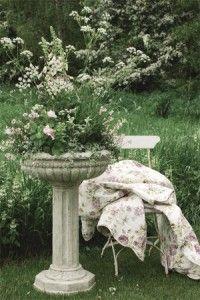Love this birdbath turned planter in a very romantic garden.