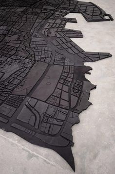 Beirut Caoutchouc by Marwan Rechmaoui, is a large black rubber floor mat in the shape of Beirut's current map. Embossed in precise detail with roads and byways and segmented into 60 individual pieces demarcating neighborhoods. Rechmaoui's installation scrutinizes the physical and social formation of one of the world's most conflicted cities.