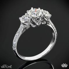 "Elegance is redefined with this magnificent ""Swan"" 3 Stone Engagement Ring. The graceful lines twist and swirl to create an extraordinary sanctuary for your diamonds, which will allow for maximum exposure and total security. The sides of the shank sparkle with 36 Round Brilliant Diamond Melee (0.30ctw"