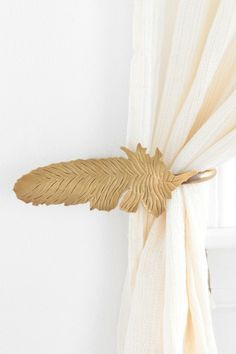Magical Thinking Feather Curtain Tie-Back  I wish this came in silver for my bedroom!  I might have to buy and paint it....