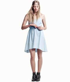Dress in washed denim that is slightly longer at the back with thin shoulder straps, a racer back, and fastener at the back. Elasticated at the waist and gently flared to the hem.