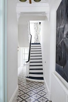 """Suzy Hoodless has opted for a smart monochrome palette in the hall of [link url=""""http://www.houseandgarden.co.uk/article/suzy-hoodless-hackett-holland-notting-hill-town-house""""]this Notting Hill town house[/link]. Alternating black and white paint is an easy trick for enlivening a wooden staircase. Reclaimed tiles have been used on the floor."""