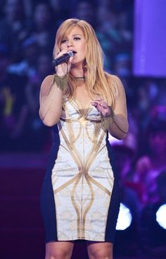 """Kelly Clarkson not only wowed the MMVA crowd with her show-stopping performance of """"Stronger"""" and Dark Side"""" but her form-fitting futuristc dress had people talking. The former """"American Idol"""" winner look gorgeous in the optical illusion frock which showed off her curves. Sporting her new blond locks, the singer looked fresh and excited to be in Toronto. (Photo by George Pimentel/WireImage)"""
