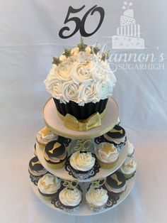 Cupcake display to celebrate a 50th birthday in black, white, and gold. Giant cupcake has a black chocolate liner, gold fondant bow tie, and a 50 cardstock topper. Cupcakes have a variety of toppers including 50 cardstock picks with bow ties, fondant wine glasses, and fondant stars. Keywords: man, male, anniversary, damask.