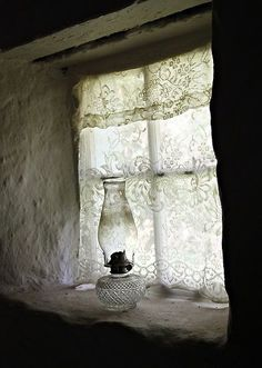 Old paned window with oil lamp