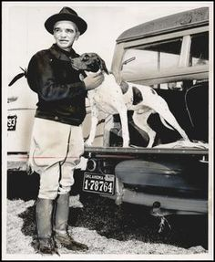 """Irvey Ownbey, 1948 (see other photo for identification).  """"Man pets his dog while it is standing on tailgate of car."""" Photographer: Bob East. Oklahoma Publishing Company Photography Collection. """"The Gateway to Oklahoma History"""" online."""